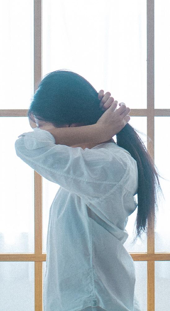 鍵岡龍門撮影の髪を束ねる女性