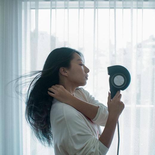 カドークオーラBD-E1ヘアドライヤーで髪を乾かす女性