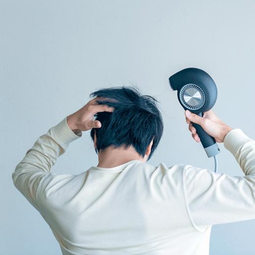 カドークオーラBD-E1ヘアドライヤーで髪を乾かす男性